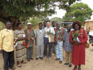 Paul Tench , with Meta cap, Meta bag and Meta plant of peace, with the Fon and other leaders; MercyAnn Nduku on the right